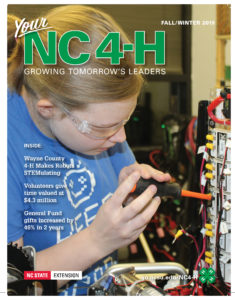 Cover page of NC State Extension's North Carolina 4-H: Growing Tomorrow's Leaders magazine for Fall and Winter 2019, which shows a young girl wearing protective glasses while working on a circuit board